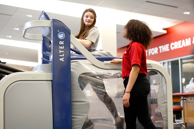 A student observes someone walking on a treadmill.