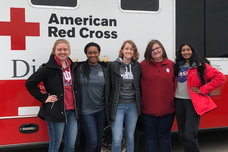 Students stand in front of an American Red Cross vehicle.
