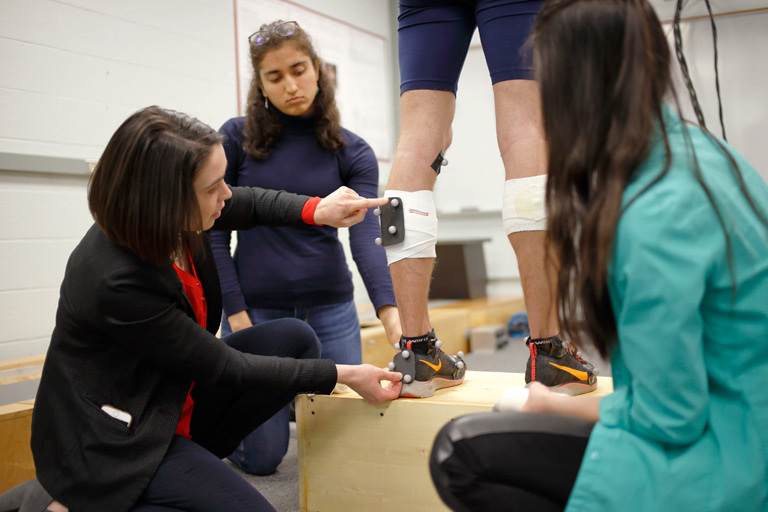Students attach monitoring equipment to another student's legs.