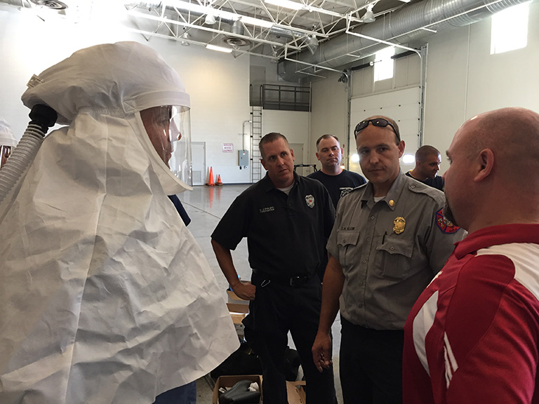 A person in a hazmat suit speaks with a group of first responders.