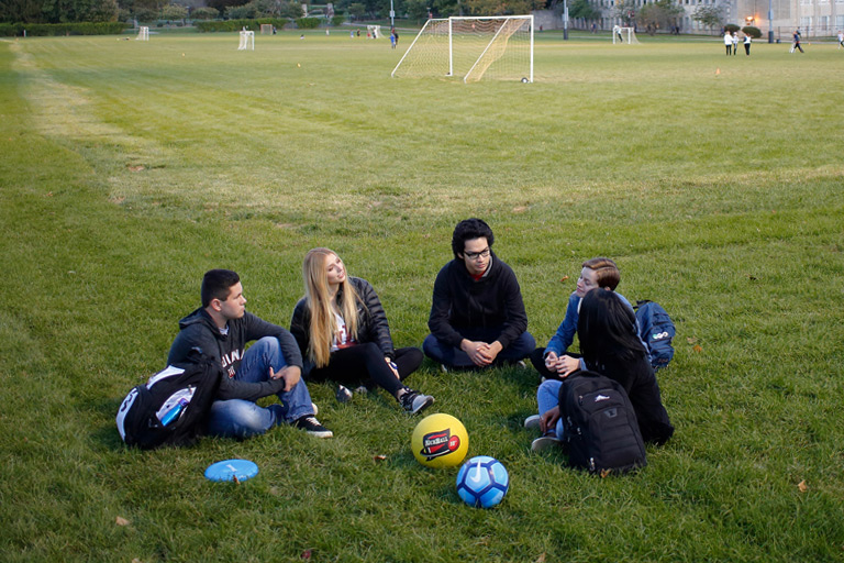 A few students talking on a soccer field.