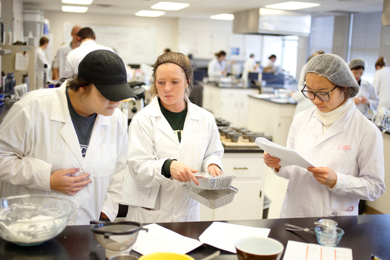 Students in lab coats prepare food.