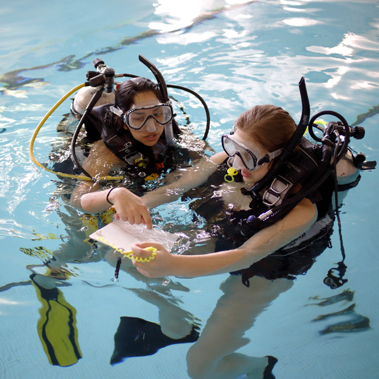 Two students wearing diving equipment in a swimming pool.