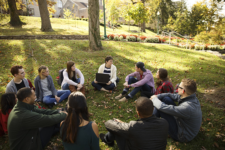 A class sits in a circle on the grass.
