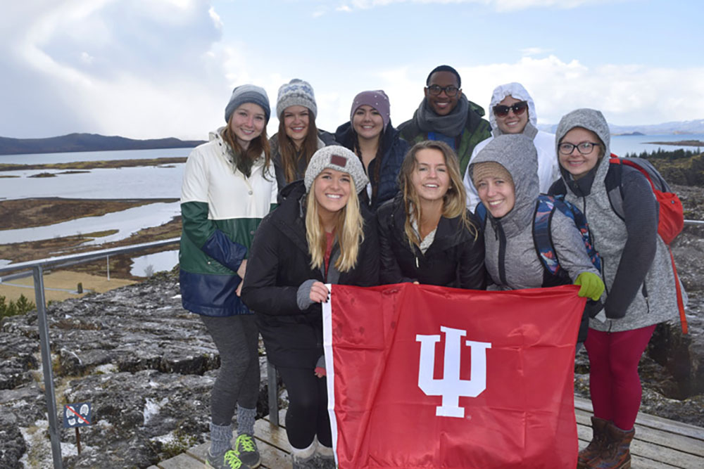 Students wearing winter clothes hold up an IU flag.