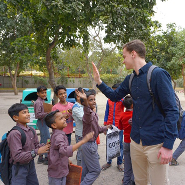A student high fives a child walking past.